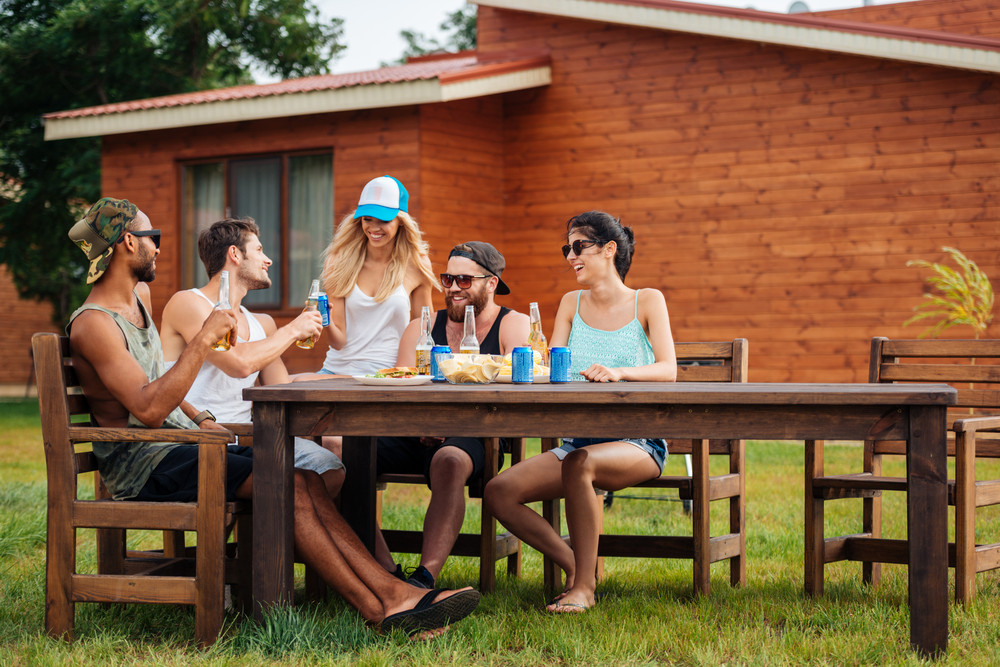 Group of smiling young people drinking beer and soda at the table outdoors