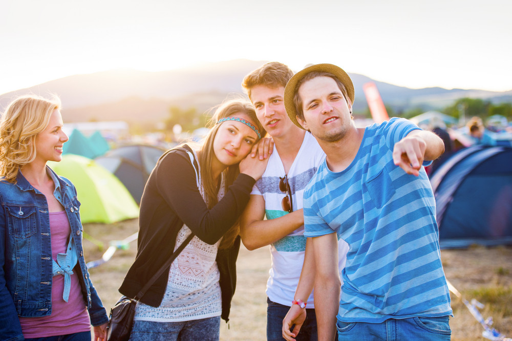 Group of teenage boys and girls at summer music festival, couple in love, sunny day