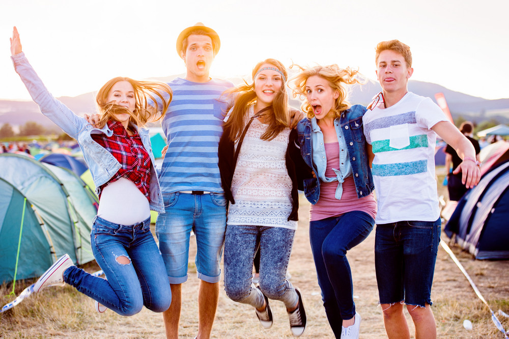 Group of teenage boys and girls at summer music festival, jumping, sunny day