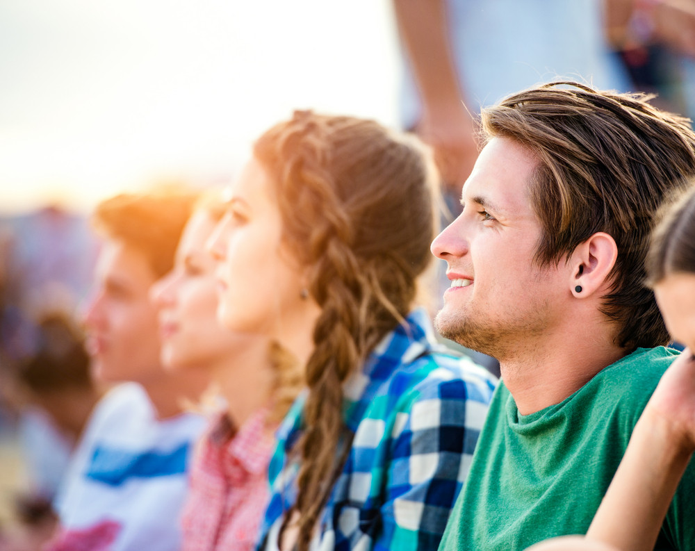 Group of teenage boys and girls at summer music festival, sitting on the ground,  hipster boy in green t-shirt