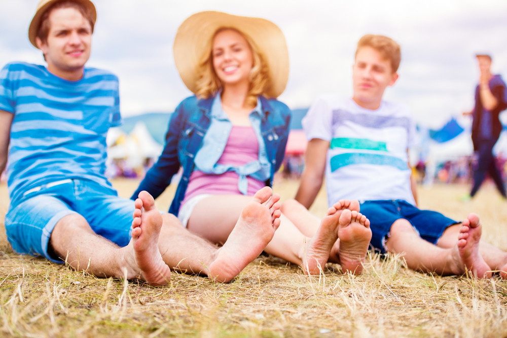 Group of teenage boys and girls at summer music festival, sitting on the ground