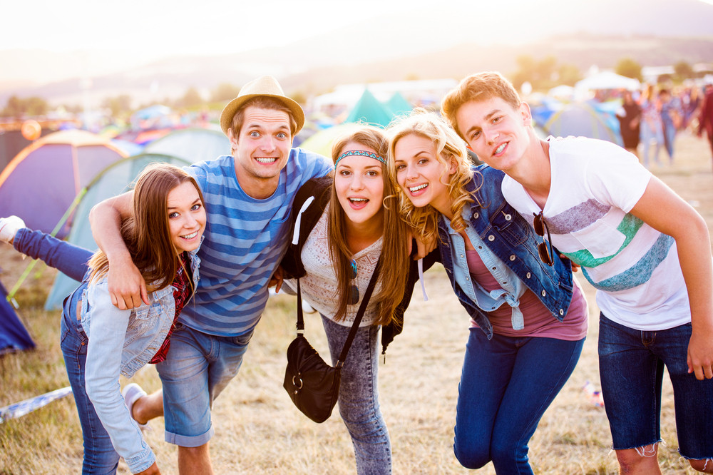 Group of teenage boys and girls at summer music festival, sunny day