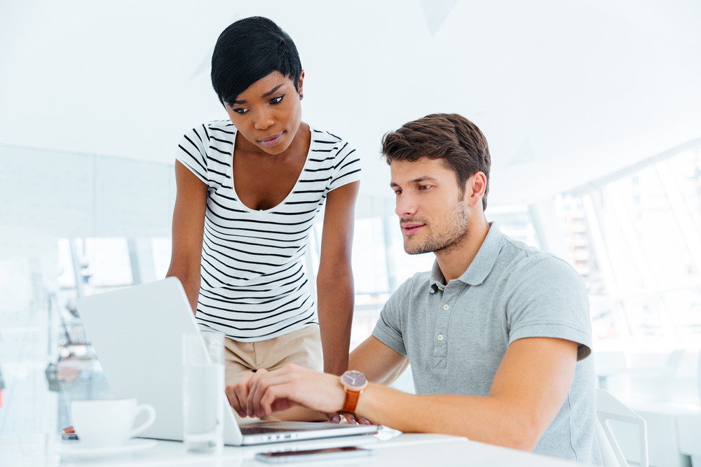 Group of two serious young business people sitting and creating business plan in office