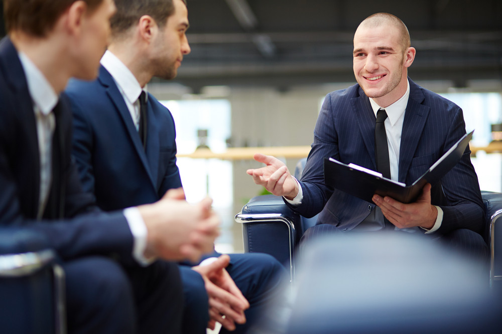 Group of young businessmen communicating at meeting