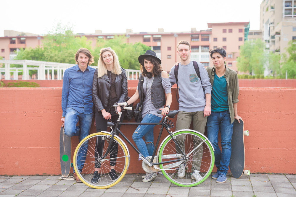 Group of young multiethnic friends posing leaning on a  wall holding skateboards and bicycle , smiling looking in camera- friendship, sport concept