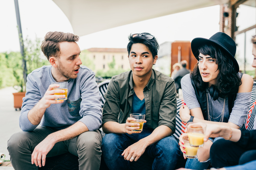 Group of young multiethnic friends sitting in a bar having a drink, talking to each other, having fun - happy hour, friendship, relax concept