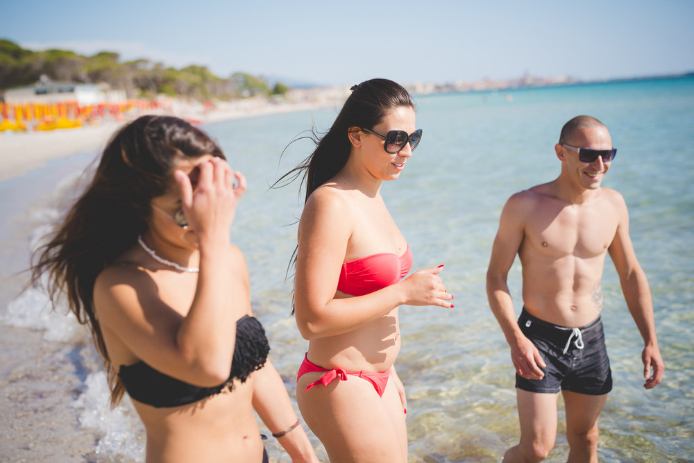 group of young multiethnic friends women and men at the beach in summertime