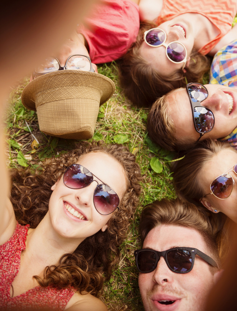 Group of young people having fun in park, lying on the grass
