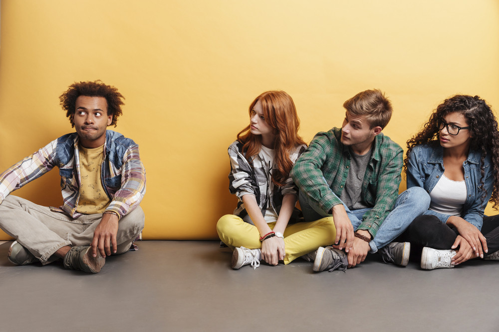 Group of young people sitting and looking at pensive african american man over yellow background