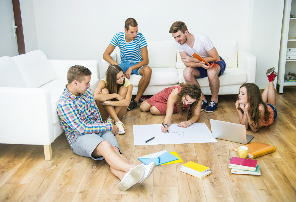 Group of young students studying together and preparing for exams in home interior