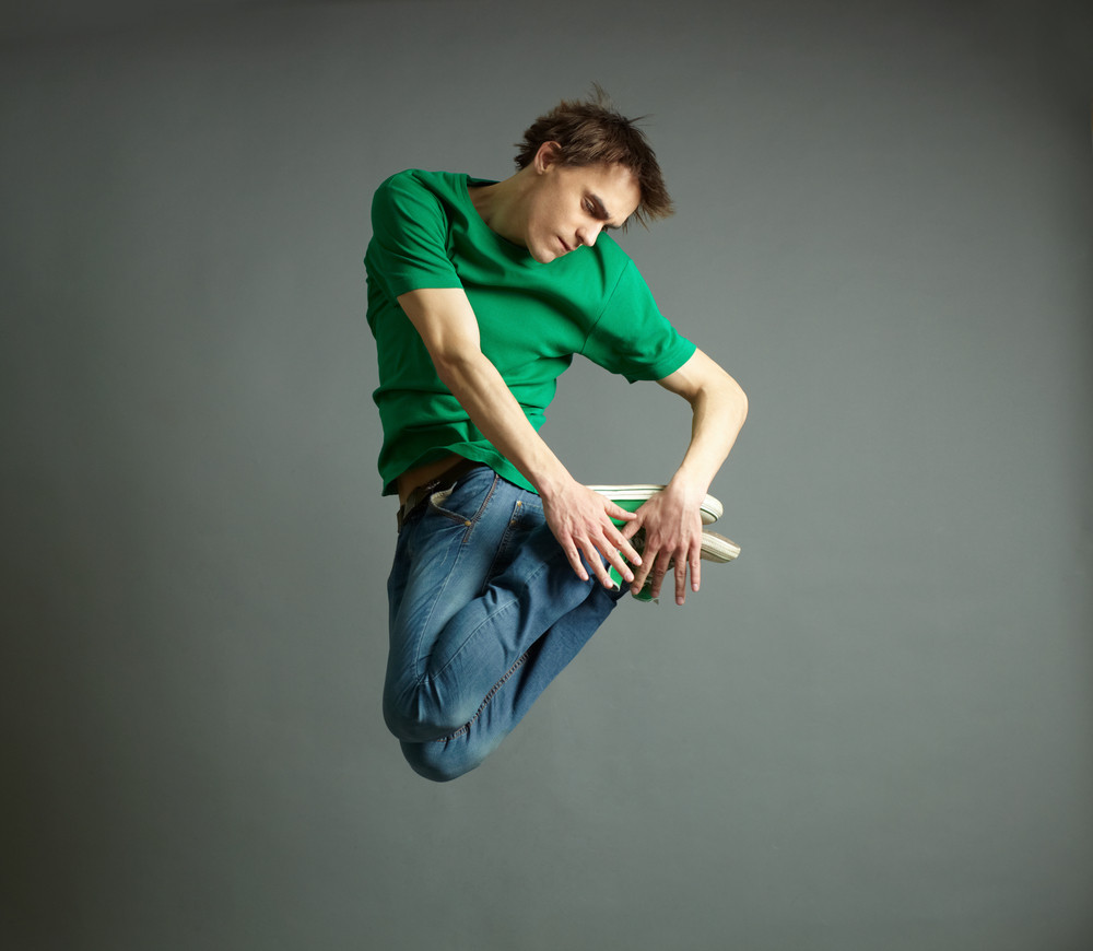 Guy in casual outfit performing a tricky twisted jump