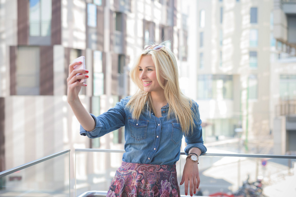 Half lenght of a young beautiful blonde caucasian girl using a smartphone taking a selfie - communication, technology, social network concept