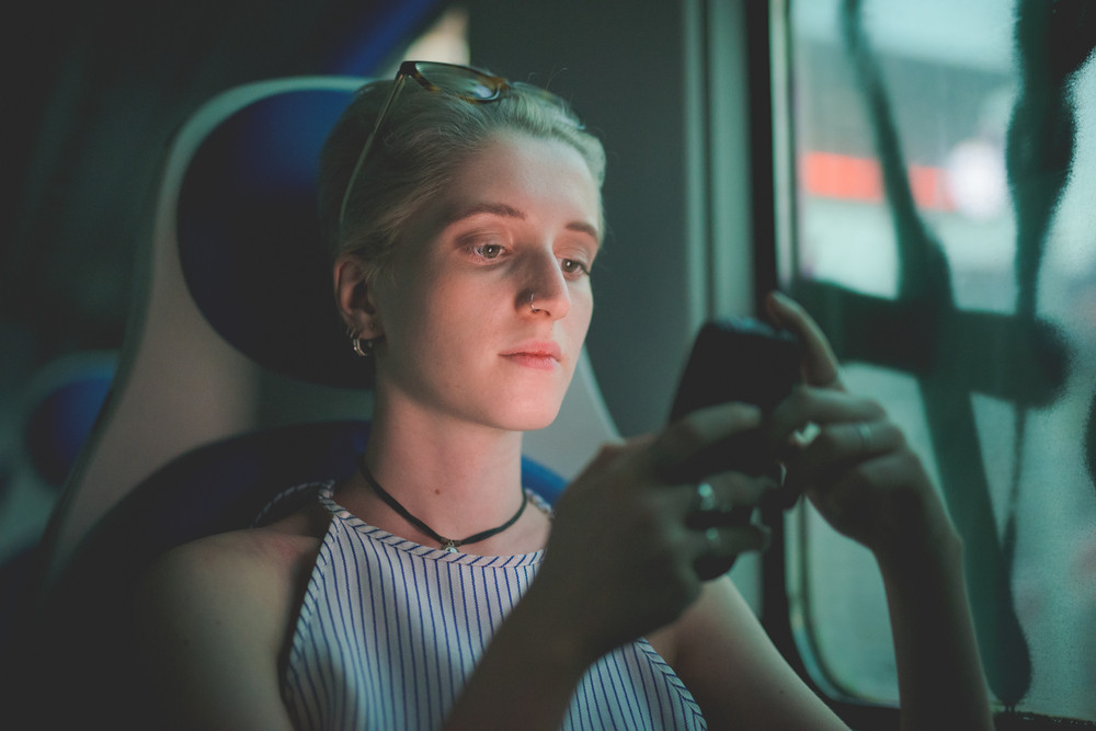half length of a young handsome caucasian blonde italian designer sitting in a train, holding a smartphone, looking down the screen, pensive- technology, social network, communication concept