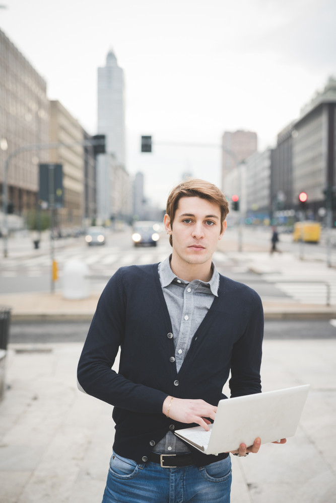 Half length of a young handsome caucasian contemporary businessman standing on the street using a notebook looking in camera - technology, network, business, finance concepts