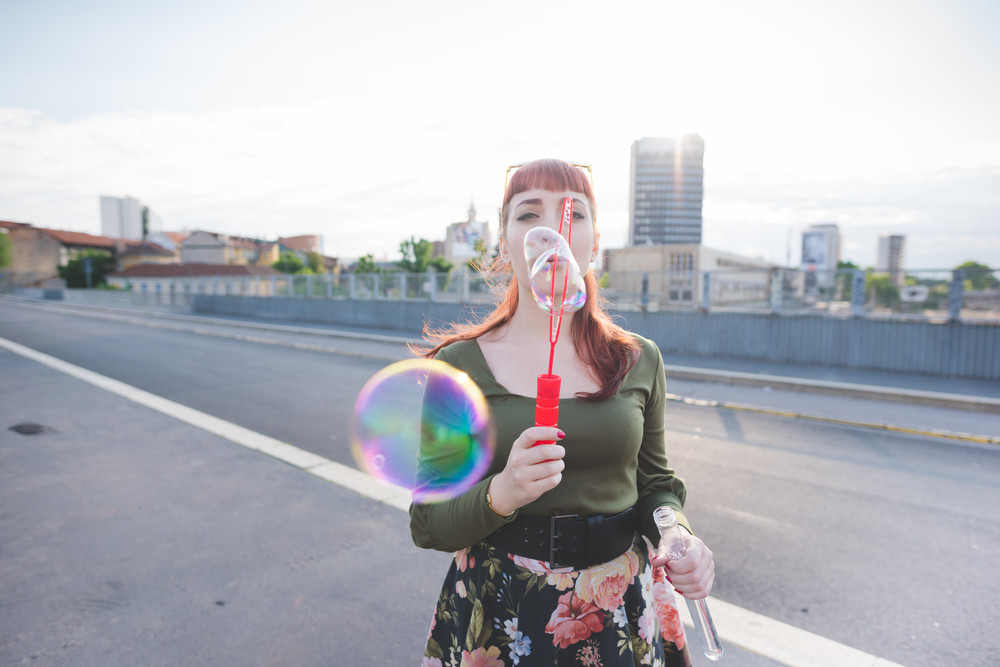 Half length of a young handsome caucasian redhead woman playing with bubble soap, blowing - childhood, youth concept - wearing green shirt