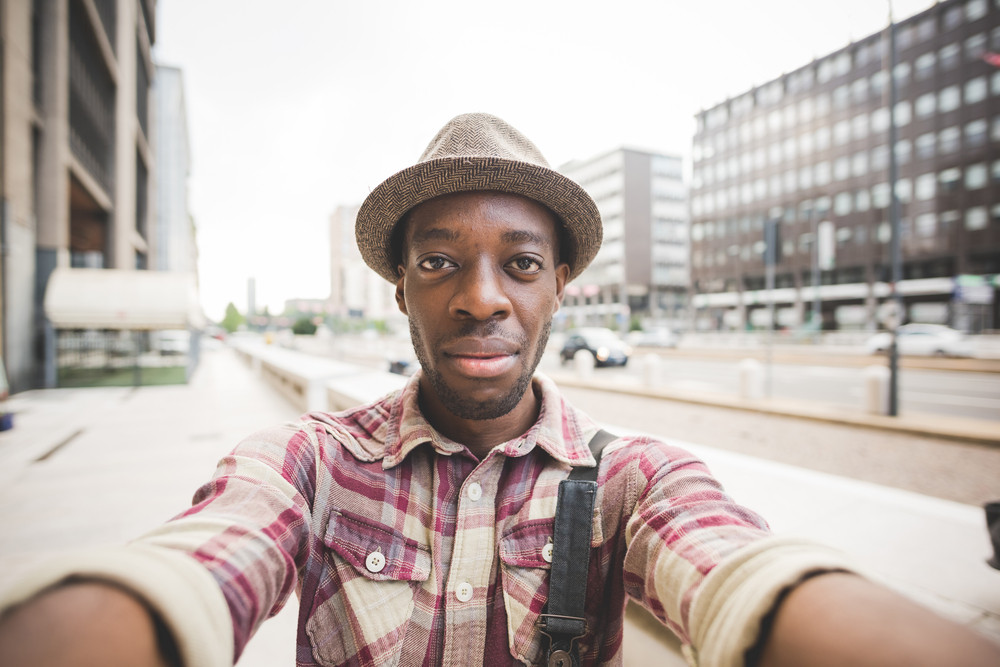 Half length of young handsome afro black man taking a selfie, looking in camera, smiling - vanity, social network concept