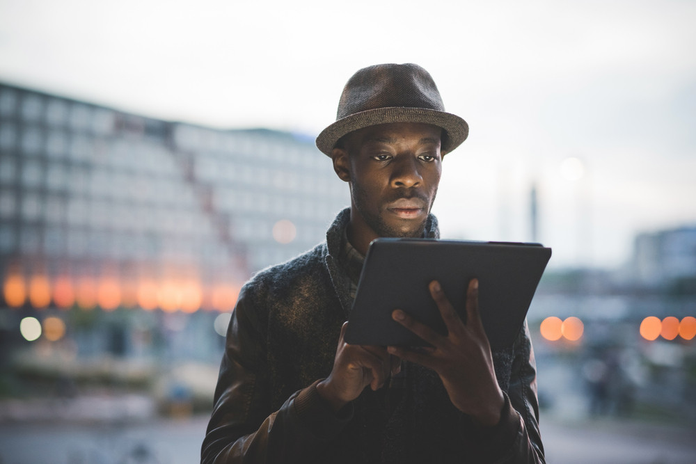 Half length of young handsome afro black man using a tablet, looking downward the screen, pensive - technology, social network, communication concept