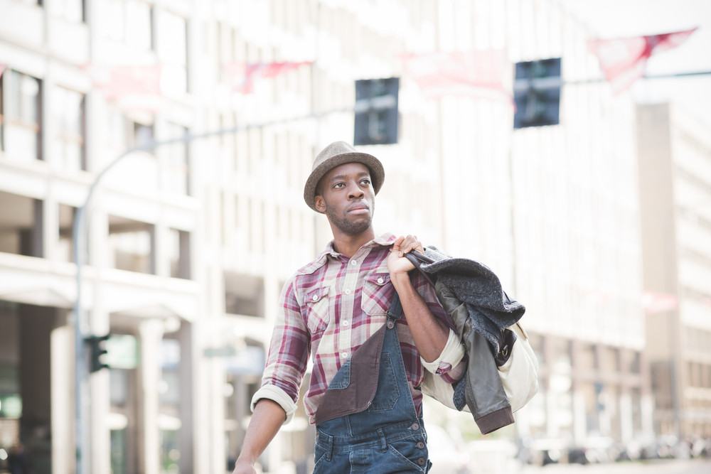 Half length of young handsome afro black man walking in the street of the city, holding a bag, overlooking left, pensive - thoughtful, thinking future concept
