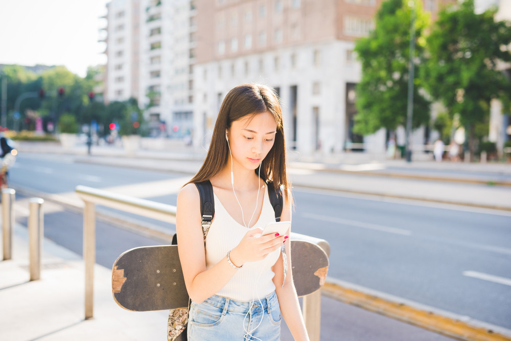 Half length of young handsome asiatic long hair woman skater walking in the city, listening music with earphones, holding smartphone looking downward and tapping the screen - music, technology concept