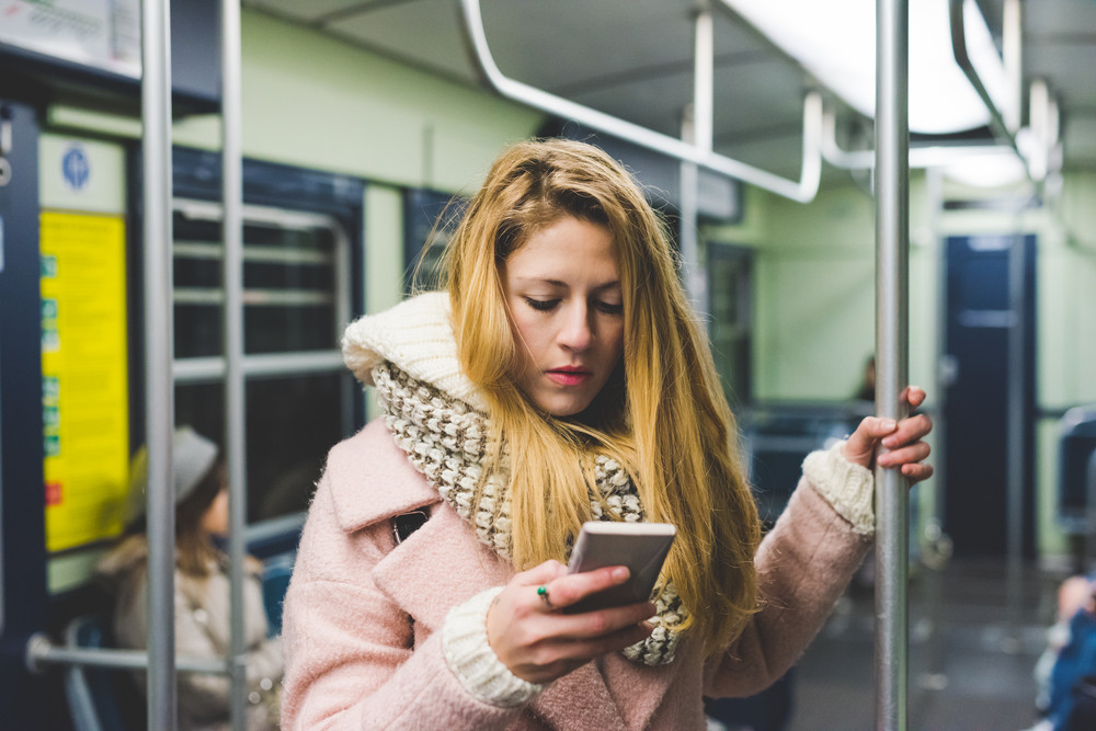 Half length of young handsome blonde straight hair woman traveling in the underground, holding a smart phone, looking down the screen - technology, commuting, transport concept