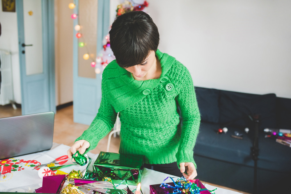 half length of young handsome caucasian woman wrapping christmas present with wrapping paper and ribbon having fun- christmas, couple, holiday concept