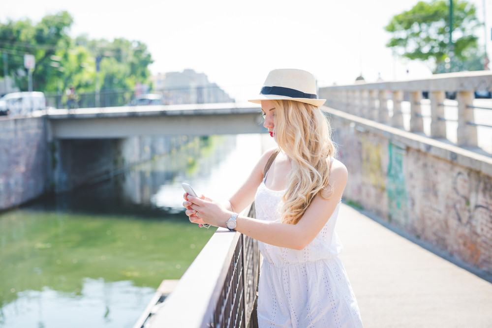 Half length of young handsome long blonde straight hair caucasian woman leaning on a handrail, using a smartphone, looking downward the screen - technology, communication, social network concept