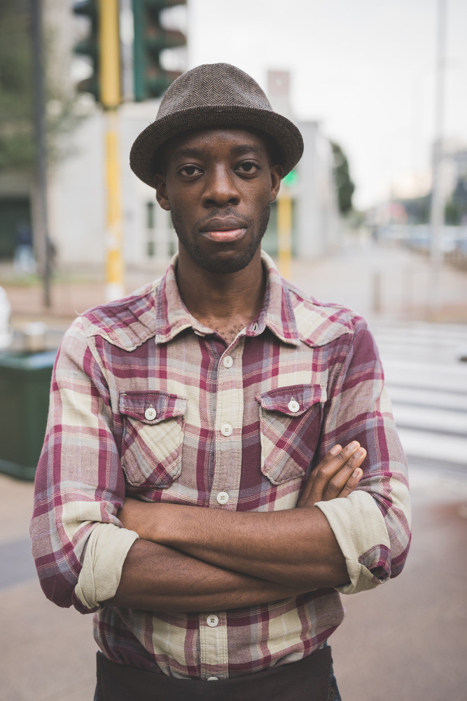 Half length portrait of young handsome afro black man looking in camera, arms crossed, pensive - thoughtful, serious, thinking future concept