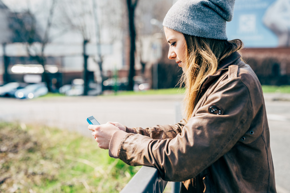 Half length side view of young beautiful caucasian woman holding a smart phone, looking down and tapping the screen - social network, communication, technology concept