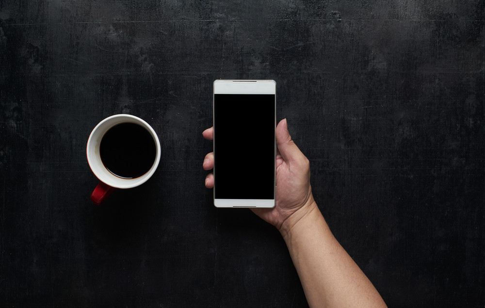 Hand holding black screen smart phone  with cup of coffee.Wooden black office desk table on top view .