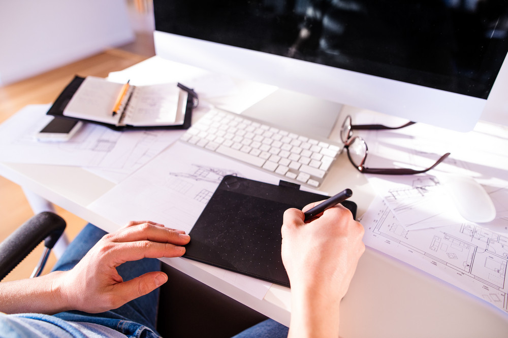 Hand of unrecognizable man working from home writing on graphic tablet