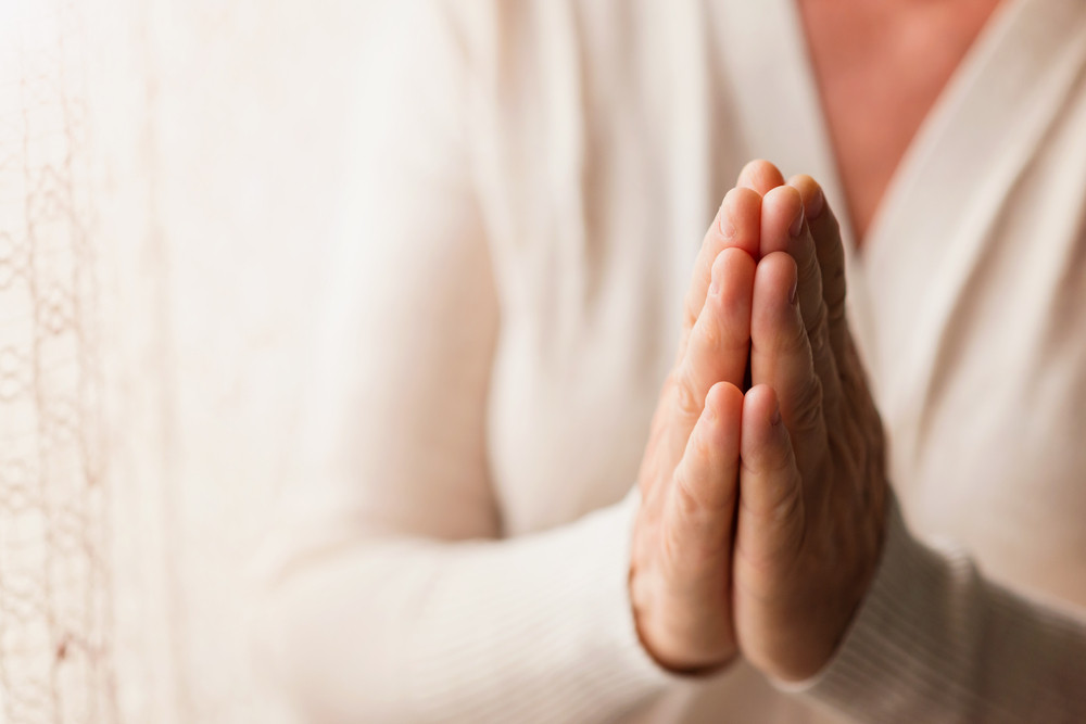 Hands of an unrecognizable woman in white cardigan praying