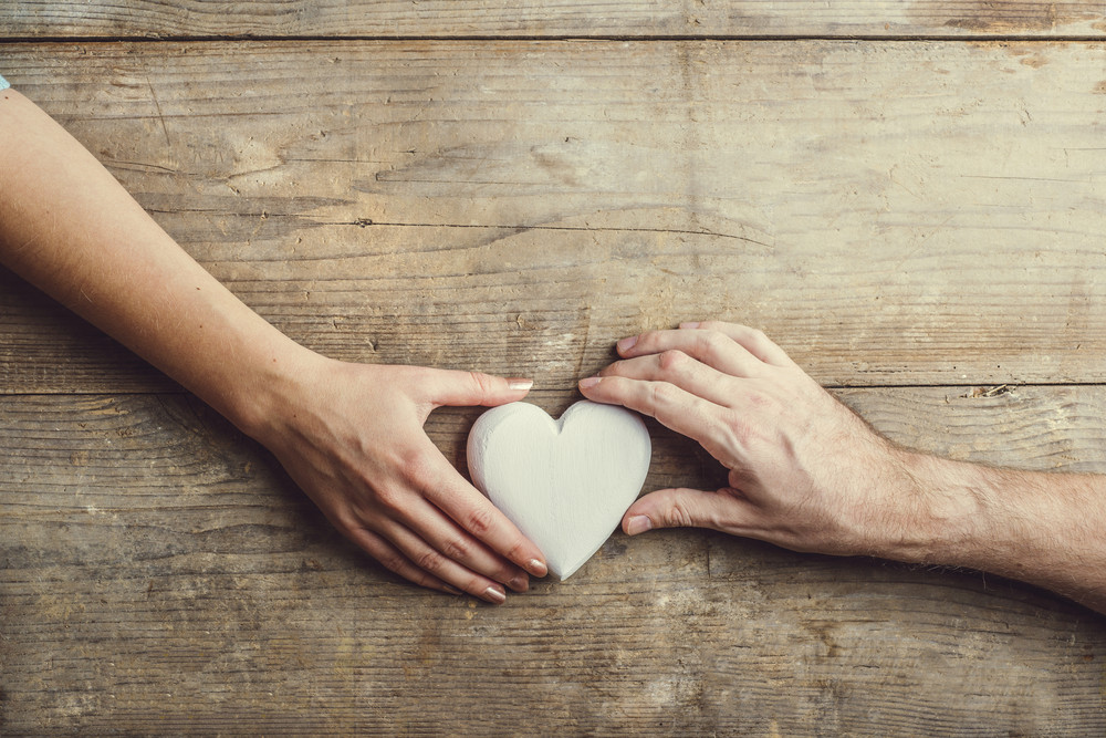Hands of man and woman connected through a white heart. Studio shot on a wooden background, view from above.