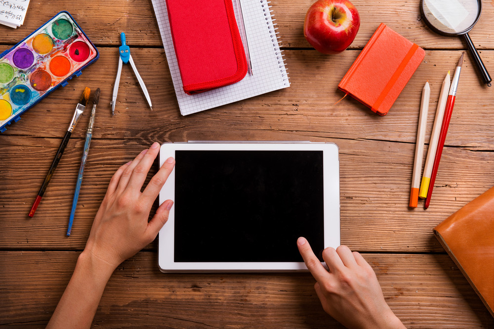 Hands of man holding tablet. Various school supplies, flat lay, copy space. Studio shot on wooden background.