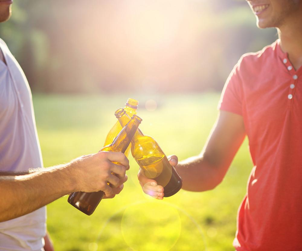 Hands of men clinnking beer bottles in park