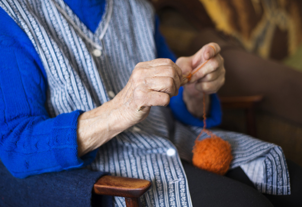 Hands of senior woman knitting with wool and knitting needles