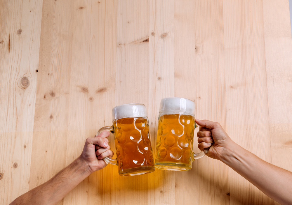 Hands of two unrecognizable men clinking with beer mugs. Oktoberfest. Studio shot on brown wooden background. Copy space.