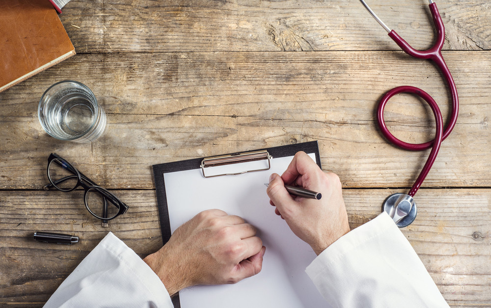 Hands of unrecognizable doctor writing on a blank sheet of paper. Wooden desk background.