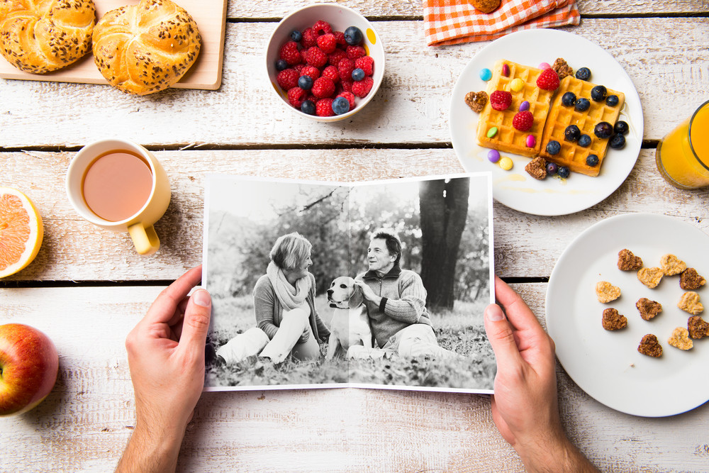Hands of unrecognizable man looking at black and white picture of senior couple. Breakfast meal laid on table. Studio shot on white wooden background.