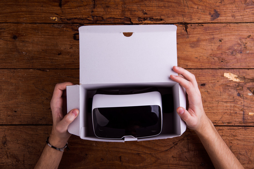 Hands of unrecognizable man unpacking virtual reality goggles from paper box. Flat lay. Studio shot on wooden background.