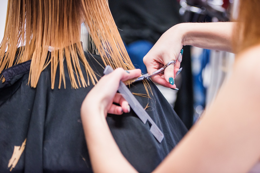 Hands of unrecognizable professional hairdresser cutting hair of her client, giving a new haircut to female customer.