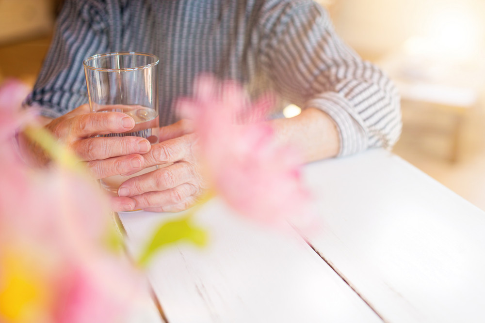 Hands of unrecognizable senior woman holding a glass of water