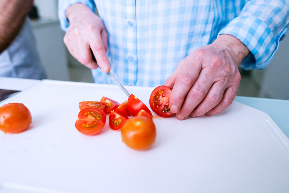 Hands of unrecognizable senior woman in checked blue shirt cutting tomatoes. Preparing breakfast.