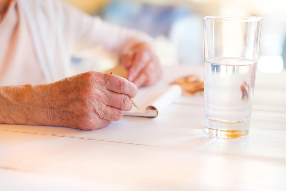 Hands of unrecognizable senior woman writing on a wooden white desk.