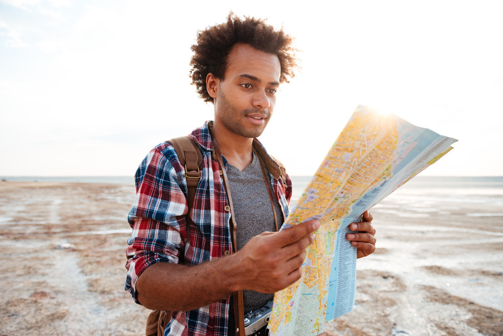 Handsome african young man in plaid shirt with map standing outdoors