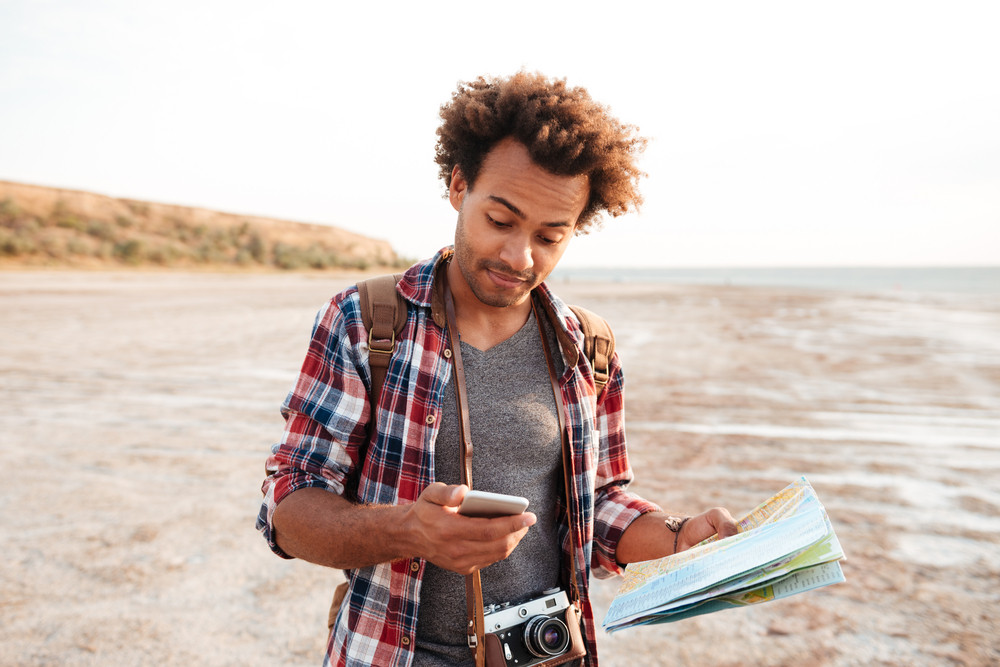 Handsome african young man with map and vintage photo camera using cell phone outdoors