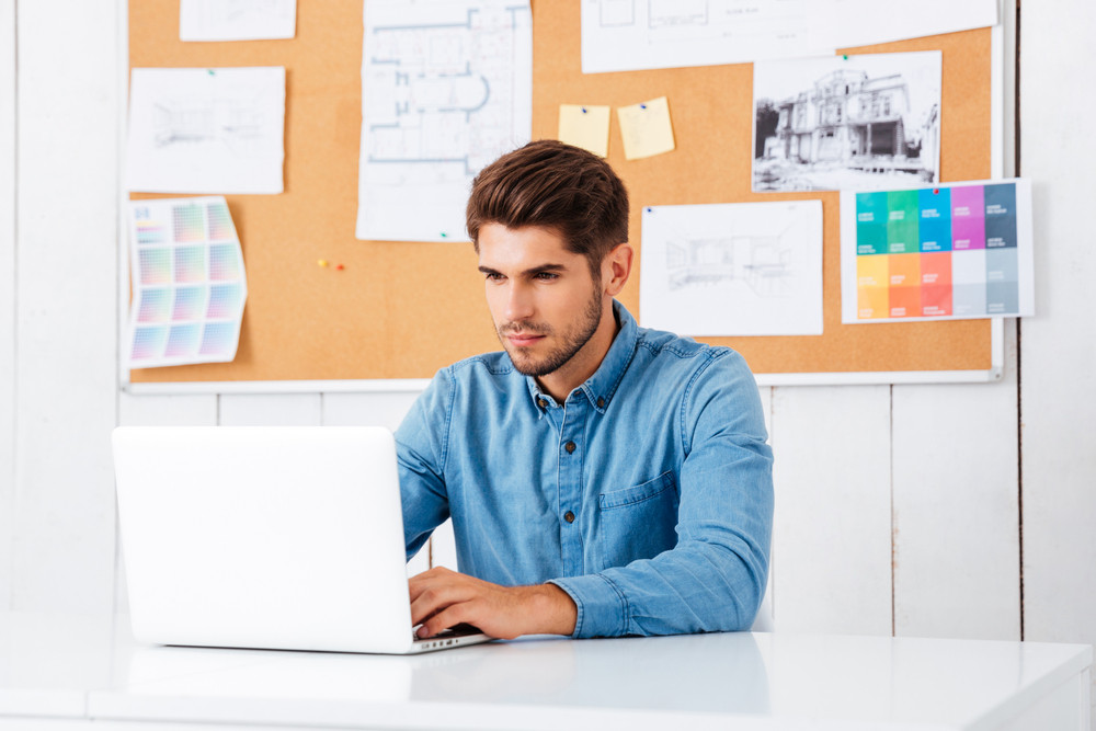 Handsome bearded casual businessman sitting with laptop at office