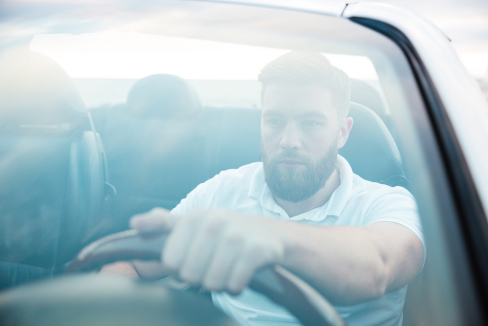 Handsome bearded man driving new car