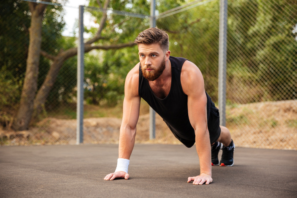 Handsome bearded young sportsman doing push-ups outdoors
