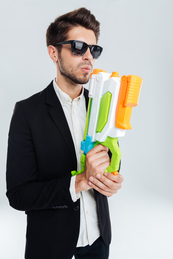 Handsome businessman in black suglasses holding colorful water gun over gray background