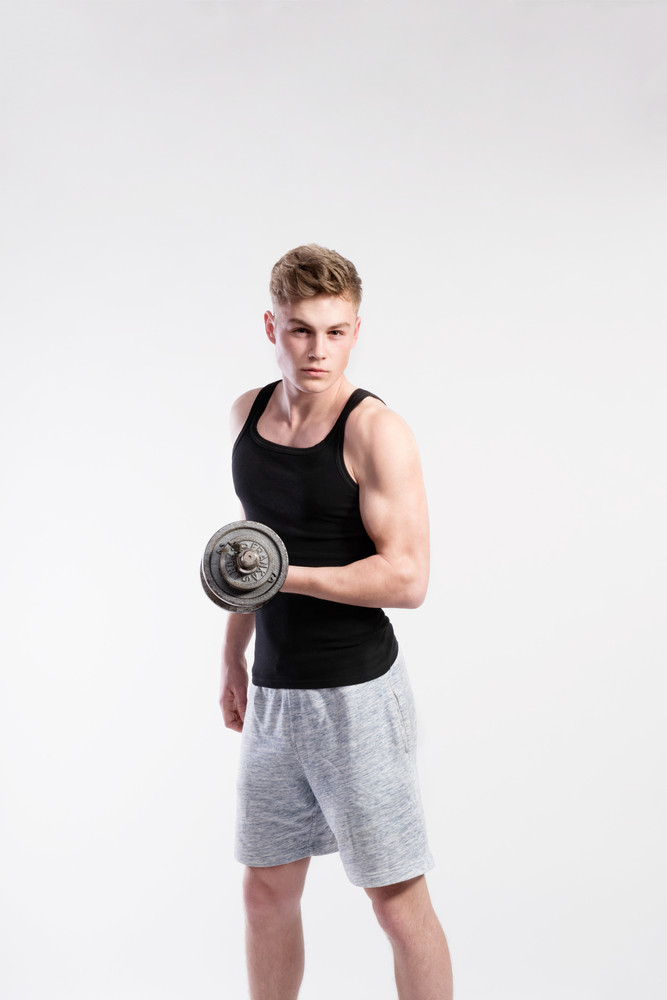 4bc682761c01a Handsome hipster fitness man in black tank top shirt working out with  dumbbell. Studio shot